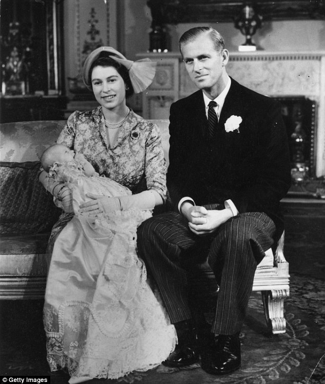 Princess Elizabeth (later Queen Elizabeth II) holding her daughter Princess Anne with the Duke of Edinburgh at her side.