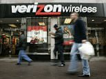 Pedestrians walk past a Verizon Wireless shop in a Washington file photo from Feb. 14, 2005. The AT&T-BellSouth deal, which would give AT&T Inc. complete control of Cingular Wireless, ups the pressure on Verizon Communications Inc., whose executives have indicated they would love to take complete control of their wireless joint venture.  (AP Photo/Charles Dharapak, File)