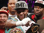 Floyd Mayweather Jr., center, celebrates after defeating Andre Berto during their welterweight title boxing bout Saturday, Sept. 12, 2015, in Las Vegas. (AP Photo/John Locher)