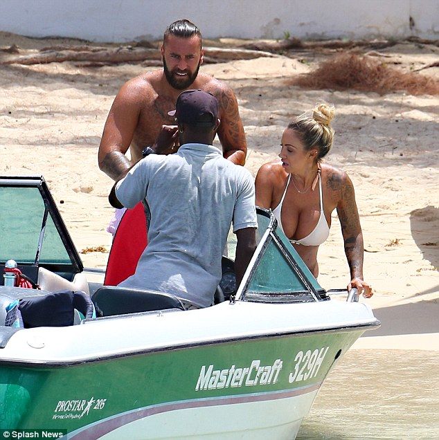 Loved up: Wearing a revealing two-piece swimsuit, the tattoed star was inseparable from her handsome man