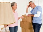 AX5CP5 Mature couple in living room with cardboard boxes, discussing