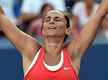 Vinci puts her hands in the air in celebration after beating fellow semi-finalist Williams 2-6 6-4 6-4