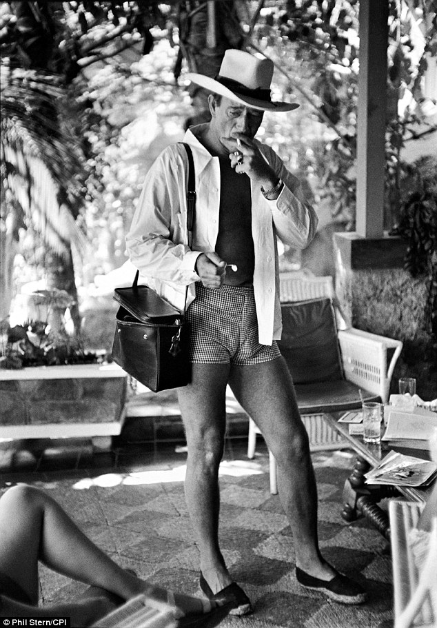 Work it, cowboy: Another one of his notable photographs is this image of Hollywood legend John Wayne smoking in shorts