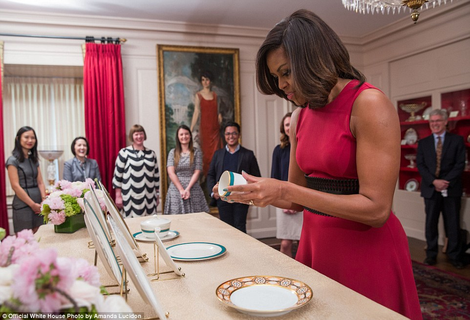 Seal of approval: Seen here inspecting the new White House china for the first time, the first lady got an 'aw' from the president when he stopped in to inspect the official state setting designed with h is island home state in mind