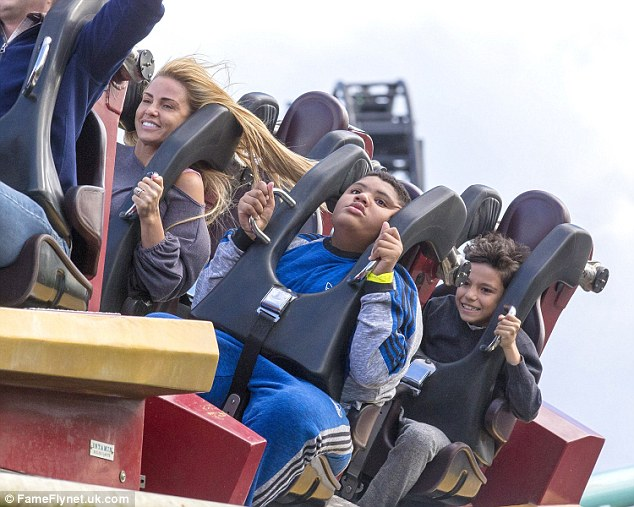Up high: Katie, Harvey and Junior held on tight as they rode the roller coaster