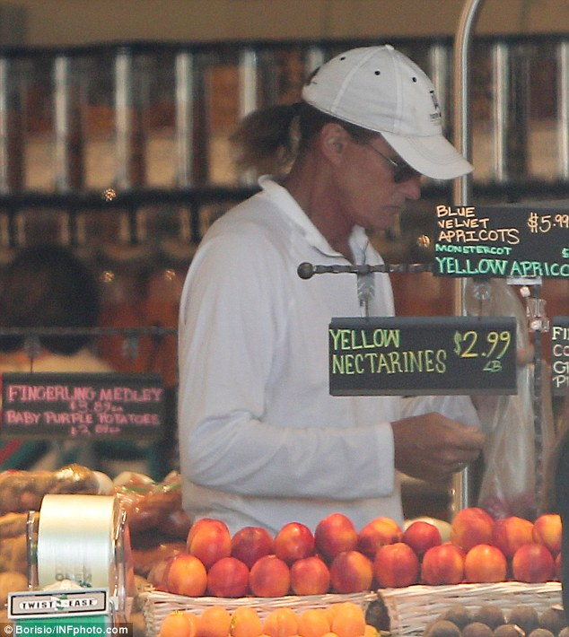 Fruit fan: Meanwhile in Malibu, their father Bruce Jenner was busy selecting ripe produce in the grocery store on Thursday