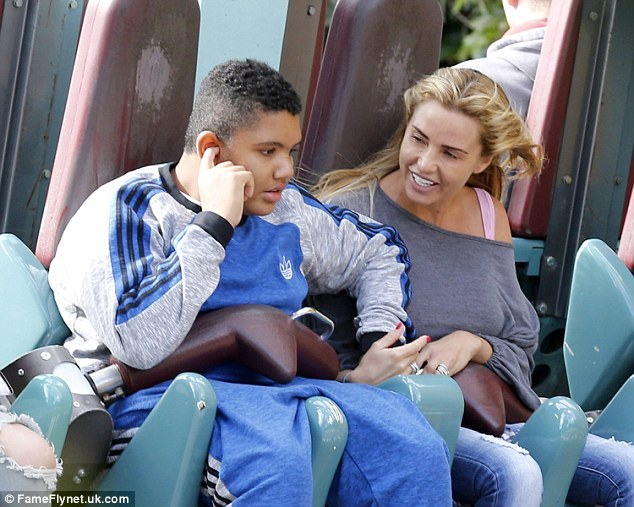 Family love: Katie held Harvey's hand as they hit up the thrill rides together