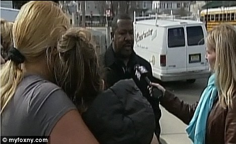 Outrage: A school official speaks to parents outside Gregory Elementary School in Long Branch, New Jersey after four boys were allegedly bound and gagged by janitors