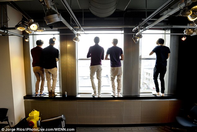 Calm before the storm: The band look down at fans outside the window in the green room ahead of their Toronto performance
