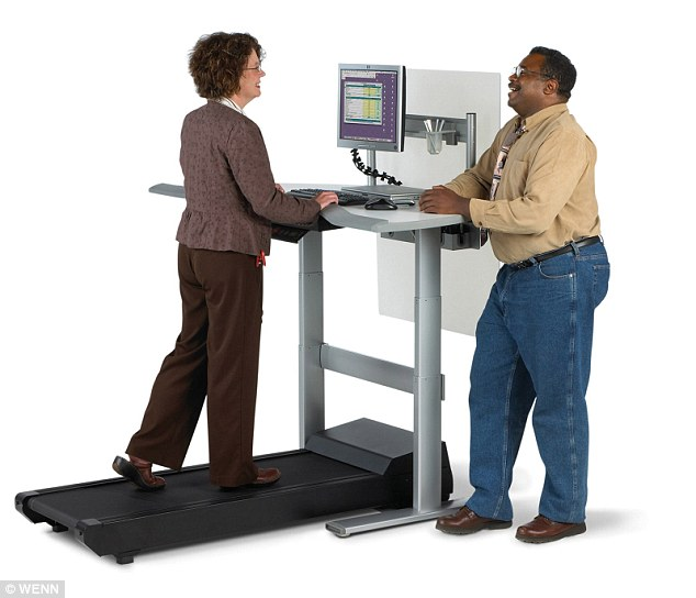 Multitasking: Standing or even walking while working can help office employees to ward off 'sitting disease' according to Dr Levine