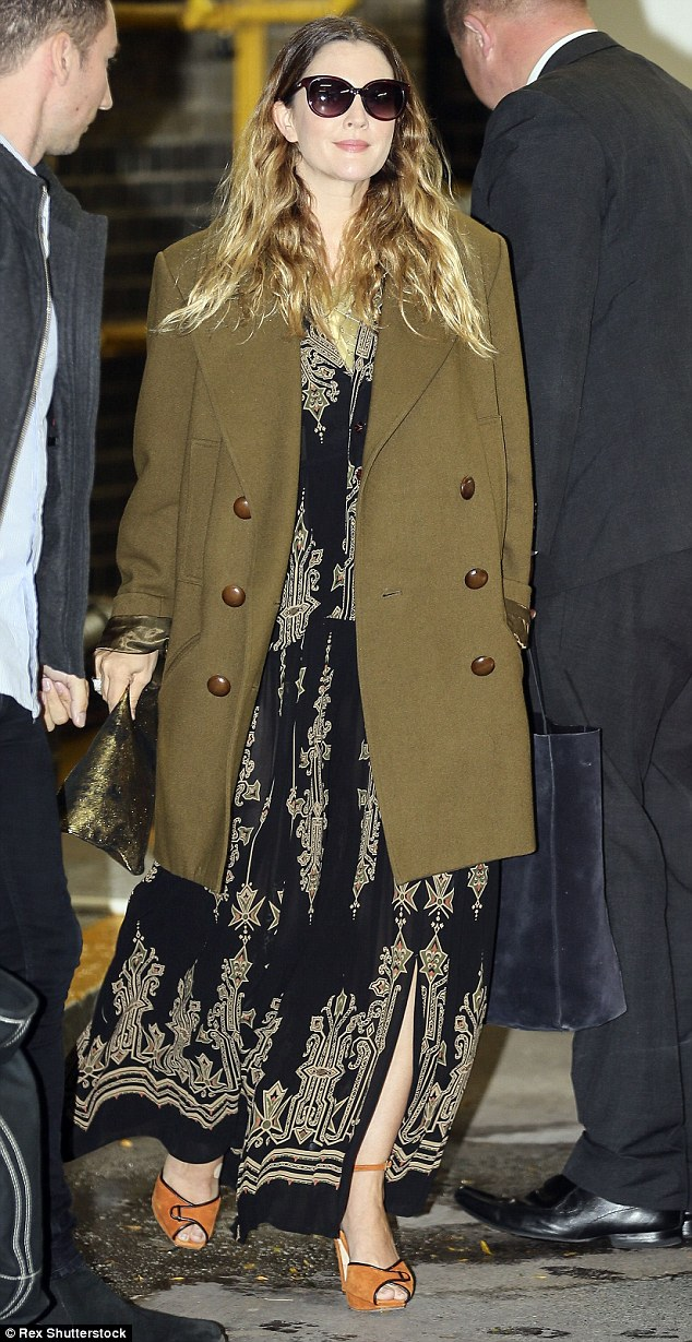 Adapting to the British weather: The mother-of-two topped her ensemble with a khaki coat