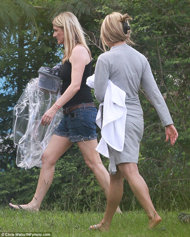 All wrapped up: Miss Aniston kept her wedding finger out of sight under a white towel as she headed across site