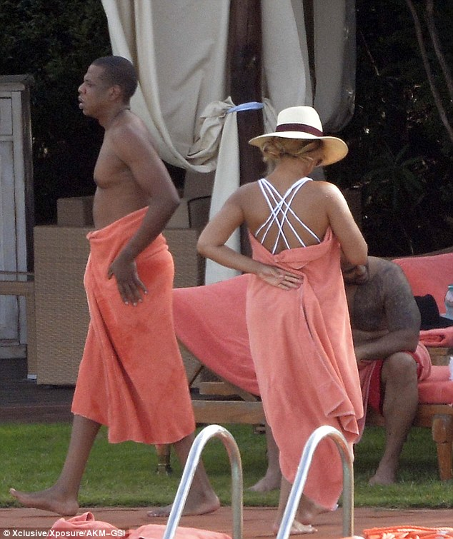 Back on dry land: The couple wrapped up in orange towels after hopping out of the pool