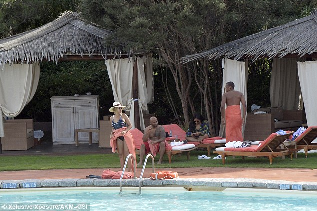 Chilling out: The duo hung out with some friends around the stunning cabanas