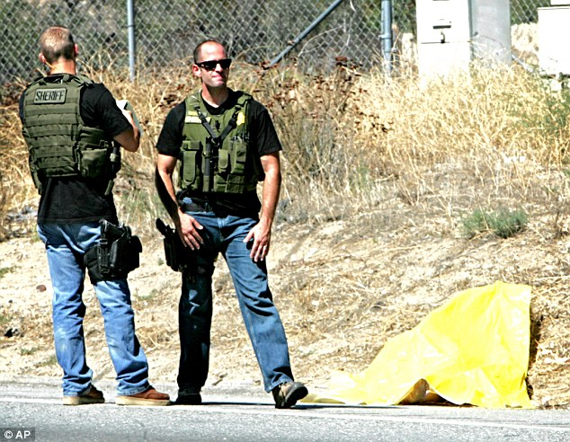 Officers today defended the shooting, saying it was a 'public safety issue' and was necessary to prevent 'more injuries to the public' (pictured, officers stand next to the suspect's body