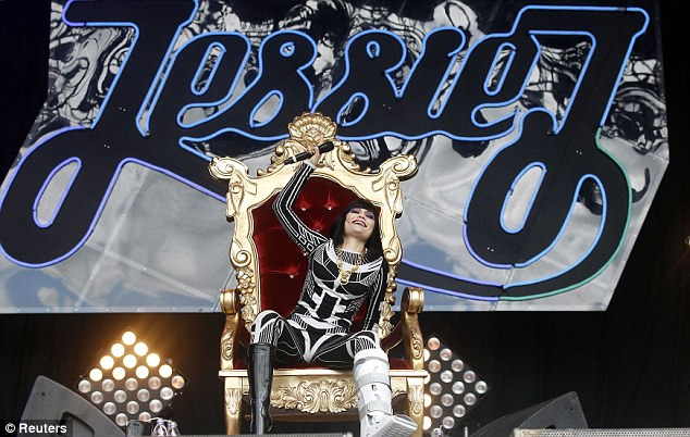 Regal wave: The star then sat down to perform on a red and gold throne to take the weight off her broken foot