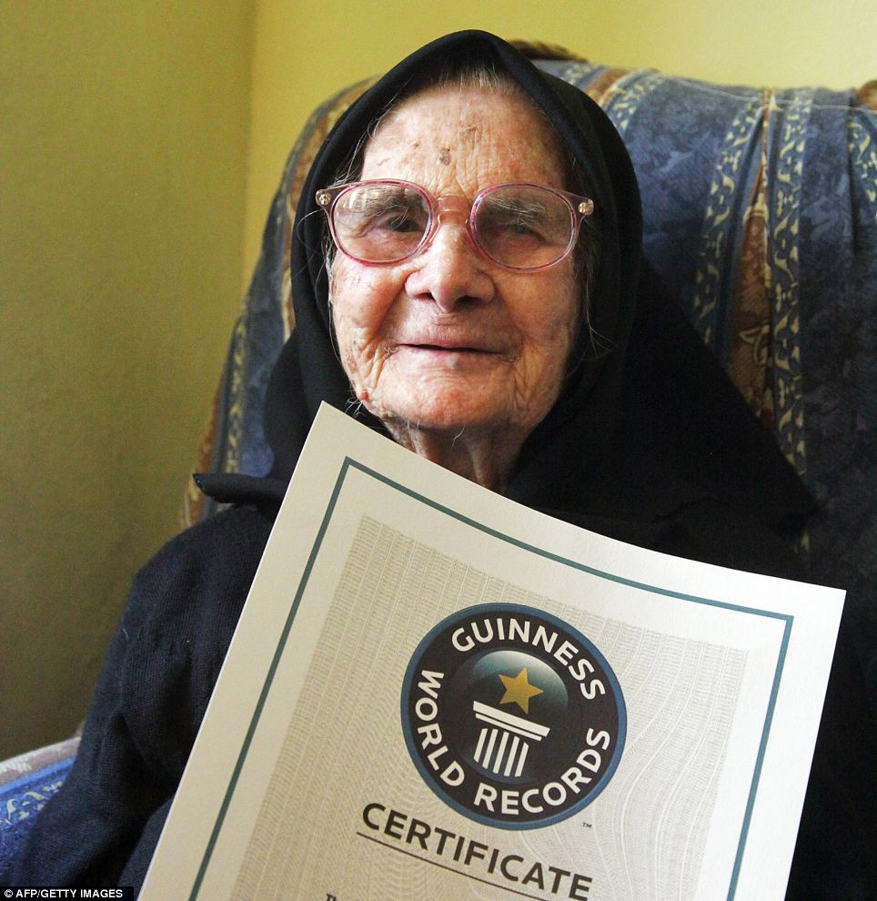 It's official: Consilata Melis proudly displays the siblings' Guinness Wolds Records certificate which states that their combined age of 818 years and 205 days makes them the oldest living siblings