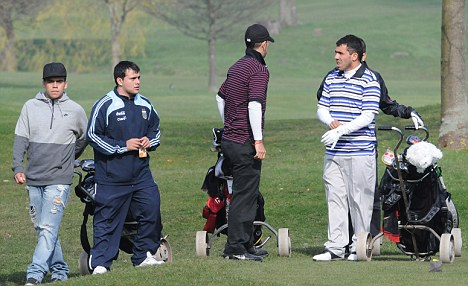 Different ball game: Tevez (right) enjoys a round the day after his City return