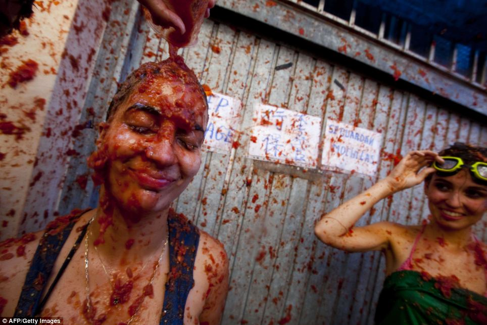 Bring it on: This girl seems resigned to her fate as a container of pulp is emptied over her head while a friend looks on