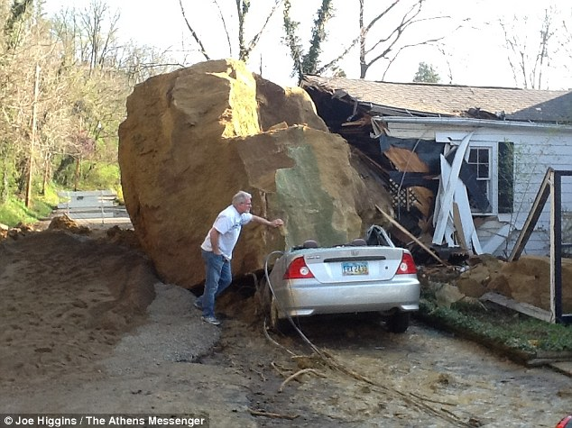 Tim Pfaff surveys the damage caused to his home and car by the boulder that fell in Athens, Ohio.