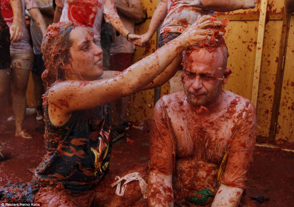Gotcha: A female festival-goer pours yet more tomato pulp on to a man's head