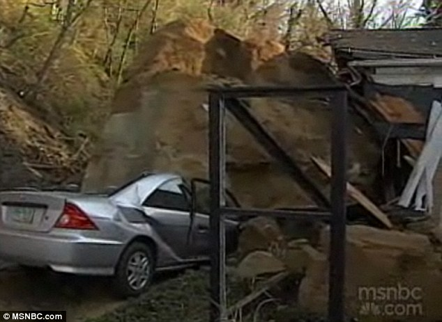 Destroyed: The family's Honda Civic was completely flattened, pictured, by the 100 ton tumbling rock on Tuesday night