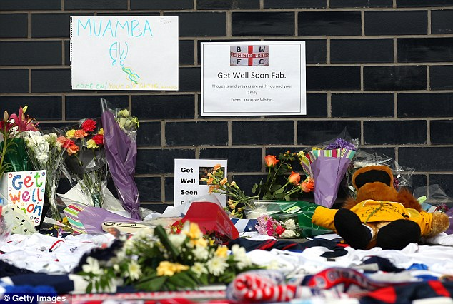 Absurd: Tributes and get well messages laid outside the Reebok Stadium. This one of many 'shrines' erected around the country, despite the fact Fabrice was not, in fact, dead