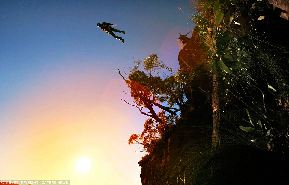 Diving into the sunset: A Base jumper leaps from the Blue Mountains in Australia before safely pulling his chute for landing