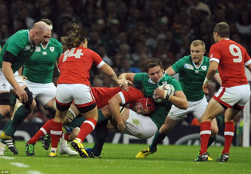 Henderson holds onto the ball after being hit with a strong challenge during the Rugby World Cup Pool D clash