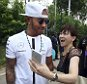 Mercedes driver Lewis Hamilton, of Britain, reacts to a fan as he arrives at the paddock before the first practice session at the Singapore Formula One Grand Prix on the Marina Bay City Circuit in Singapore, Friday, Sept. 18, 2015.(AP Photo/Ng Han Guan)