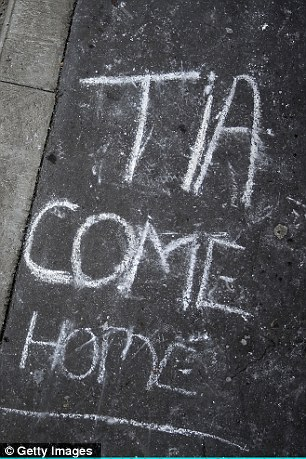 Candles, photos and messages written in chalk adorn the pavement by the bus stop where the last unconfirmed sighting of missing schoolgirl Tia Sharp was made on August 8