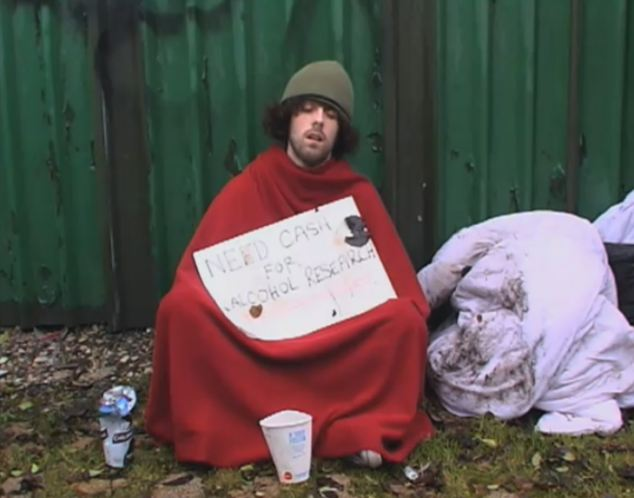 Visit Ellesmere Port: The video shows a tramp in an alleyway holding a sign reading 'Need cash for alcohol research'