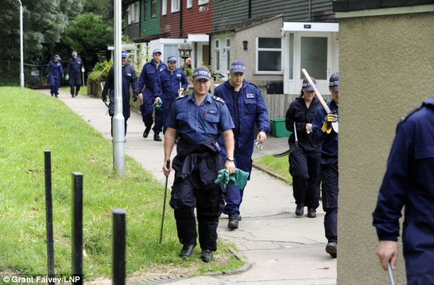 Hiding places: Police emerge from Birchwoods woodland today, which is less than a mile from Mrs Sharp's home