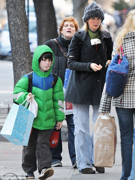 Baby love: Cynthia Nixon tucks up little baby Max inside her coat as she takes a Valentine's Day stroll with partner Christine Marinoni and Cynthia's son Charles