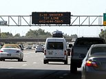 A sign still displays a shooter tip line above Interstate 10, Friday, Sept. 11, 2015, in Phoenix. Authorities have a person of interest in custody in a string of freeway shootings over the past two weeks and the man's white Chevrolet Tahoe, raising hopes of a resolution to the rash of freeway shootings rattling the metro area. (AP Photo/Ross D. Franklin)