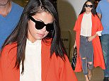 PLEASE CALL INF NYC DIRECTLY FOR USAGE at 212-582-0066 OR 917-4966. EXCLUSIVE TO INF.\nSeptember 19, 2015: Selena Gomez travels in style wearing a red trench coat, ripped skinny jeans, and stiletto heels as she arrives to Miami International Airport to catch a flight in Miami, FL.\nMandatory Credit: INFphoto.com Ref: infusmi-11/13