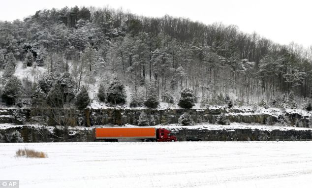 Empty: A lorry travels slowly on Interstate 65 in Alabama on Tuesday after snow fell in the area