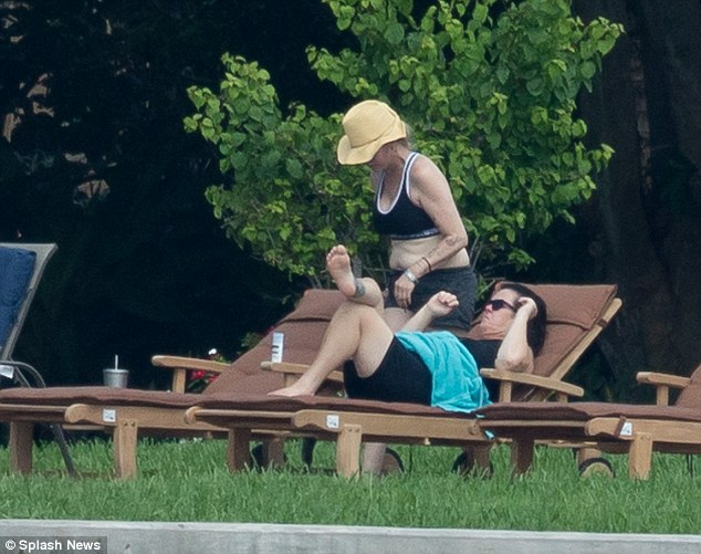 More rain is in forecast in West Palm Beach, Florida, so the couple happily sunbathed while they could during their vacation