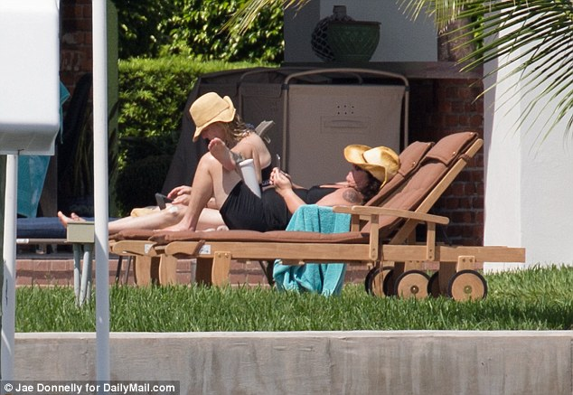 Rosie took time to check her phone as she and Tatum spent time sunbathing on Saturday