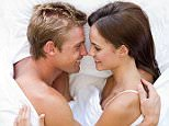 A stock photo of a Couple lying in bed smiling