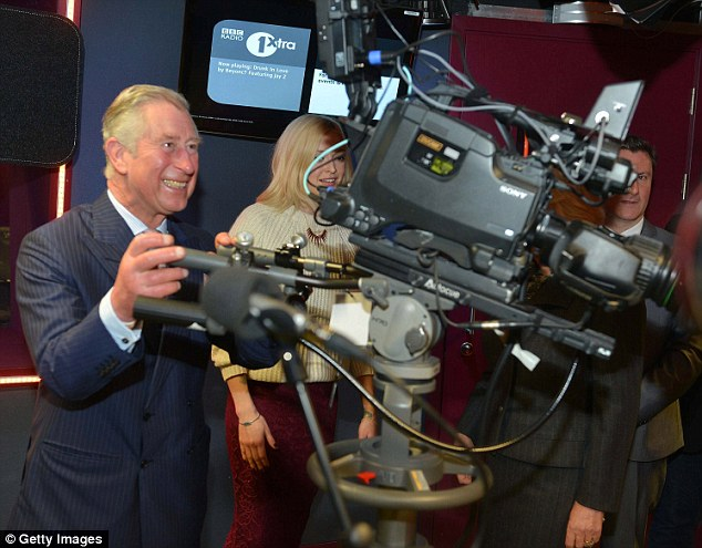 Charles, pictured at the BBC today with Fearne Cotton in the background, paid a visit to various radio stations today as part of a day to celebrate radio