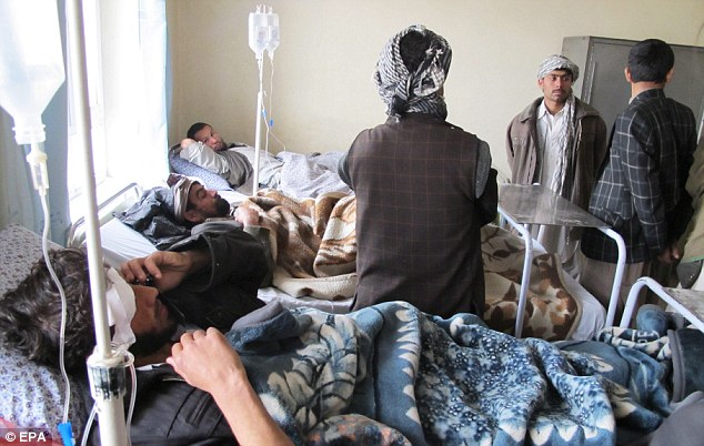 Afghan men who were among more than 40 injured in a suicide bomb attack in Imam Sahib district receive medical treatment at a local hospital in Kunduz, northern Afghanistan