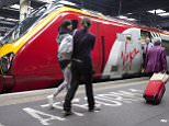 """Travellers walk to a Virgin train at Euston rail station in London.  August 15, 2012.  British billionaire Richard Branson attacked as """"insanity"""" a decision to award a key mainline train service to a rival to his Virgin Trains, drawing a parallel with other losing Virgin rail bids which he said had ended in the winners going bust. Britain's Department for Transport (DfT) said on Wednesday FirstGroup Plc had won the 13 year franchise for the West Coast line, which runs from London to Scotland, with a bid of around 6 billion pounds ($9.4 billion).REUTERS/Neil Hall (BRITAIN - Tags: TRANSPORT BUSINESS)"""