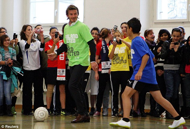 Beckham plays football with children at a school in Zurich today ahead of Thursday's crunch World Cup vote