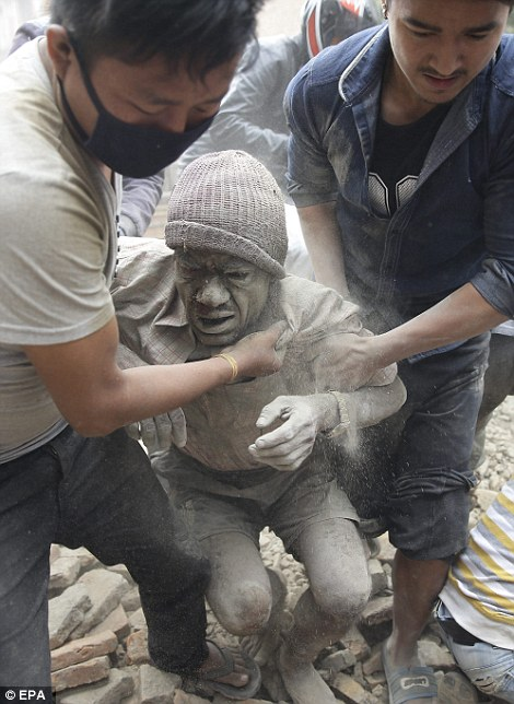 Locals rescued the dust-covered man, pulling him up on the the street as they work to find and rescue any survivors of the disaster