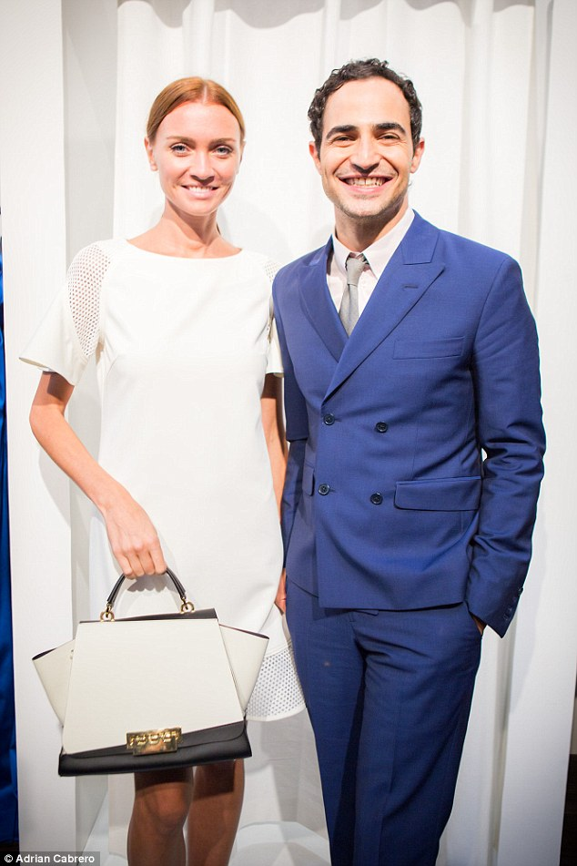 All pride: Zac poses with a model holding one of his new handbag designs at his appearance at New York's Coterie trade show