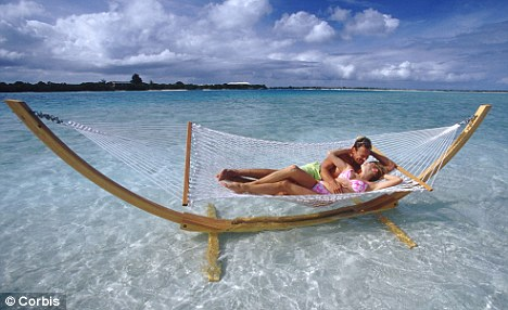 Exotic honeymoons: This couple, in the Caribbean are enjoying an extravagent break. A third of trips booked in the last year were for four weeks or more, compared with an average of just 1.5 weeks 20 years ago, it has been revealed