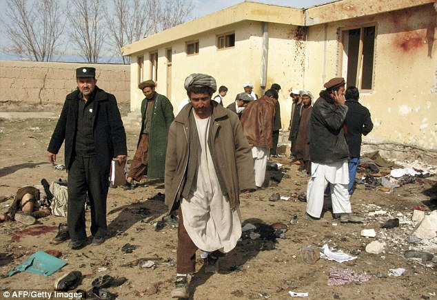 Afghan policemen and men inspect the site of a suicide attack that left more than 30 dead in northern Afghanistan on February 21, 2011