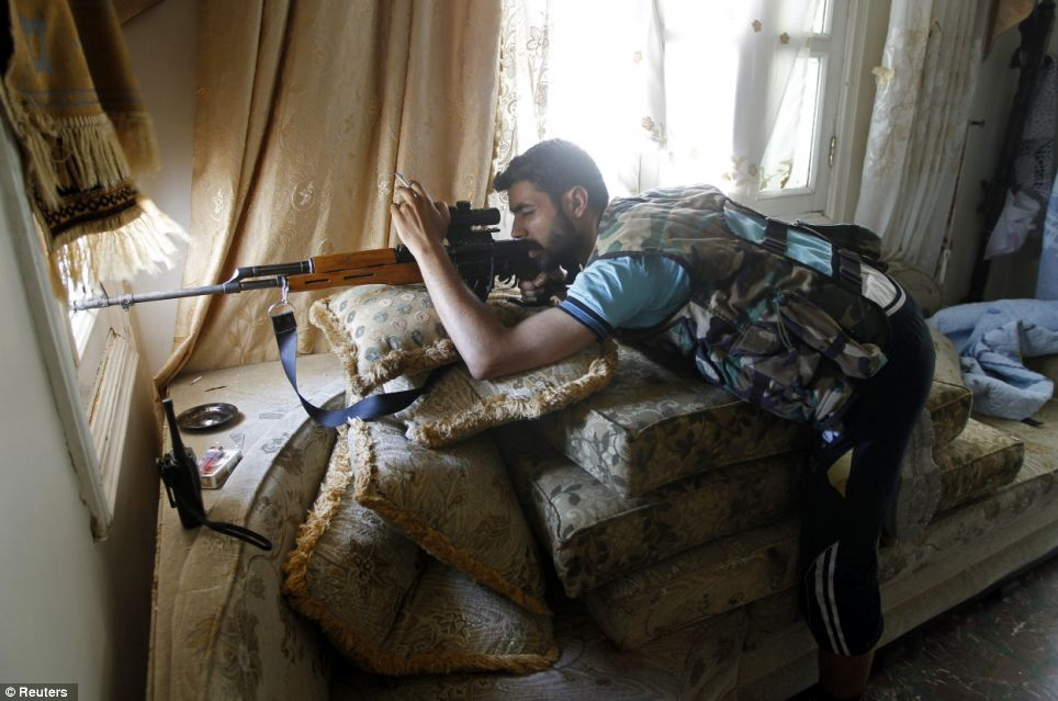 Taking aim: A Free Syrian Army sniper looks through the sight on his rifle inside a house in Aleppo