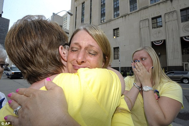 Relived victims: Geraldine Parkin, (left), 54, of Davison, Michigan, whose husband, Tim, is still alive after being over treated by Dr. Fata, hugs Cheryl Blades, (center), whose mother, Nancy LaFrance, died of lung cancer. Blades daughter and LaFrance's granddaughter, Jessica Blades, (right), 25, both of Waterford, also cries